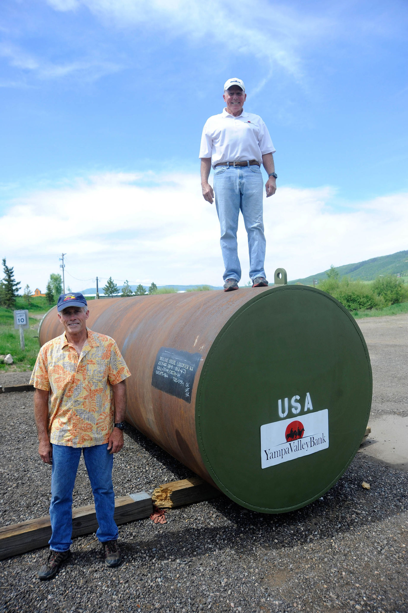 Native Excavating owner Ed MacArthur, left, and Tim Borden with the mortar tube that was buried into Emerald Mountain.